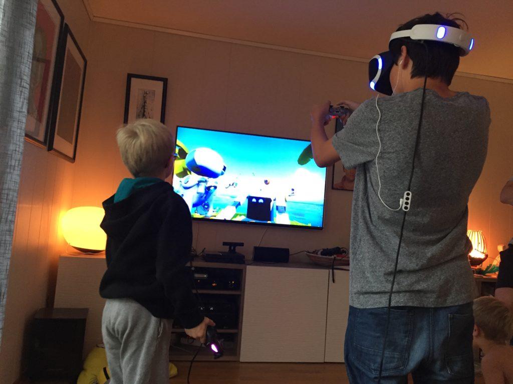 To av guttene spiller VR sammen, en med headsetttet, den andre uten.